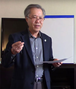 Rev. Kenneth Tanaka speaking and gesturing