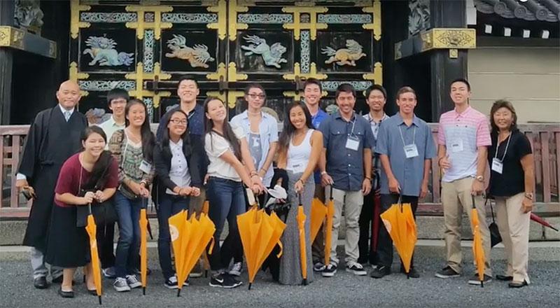 Hawaii YBICSE delegation outside Honzan holding orange umbrellas