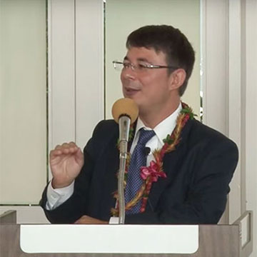 Professor Duncan Williams speaks at a podium wearing lei